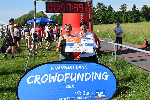 Spendenübergabe am Tag des Vegrennens: Nina Vabic nimmt den Spendenscheck am Zieleinlauf von Yvonne Schmidt entgegen