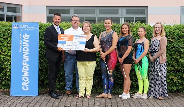 Mark Langlitz von der VR Bank Main-Kinzig-Büdingen eG überreicht den symbolischen Spendenscheck vor der Sporthalle in Langenselbold